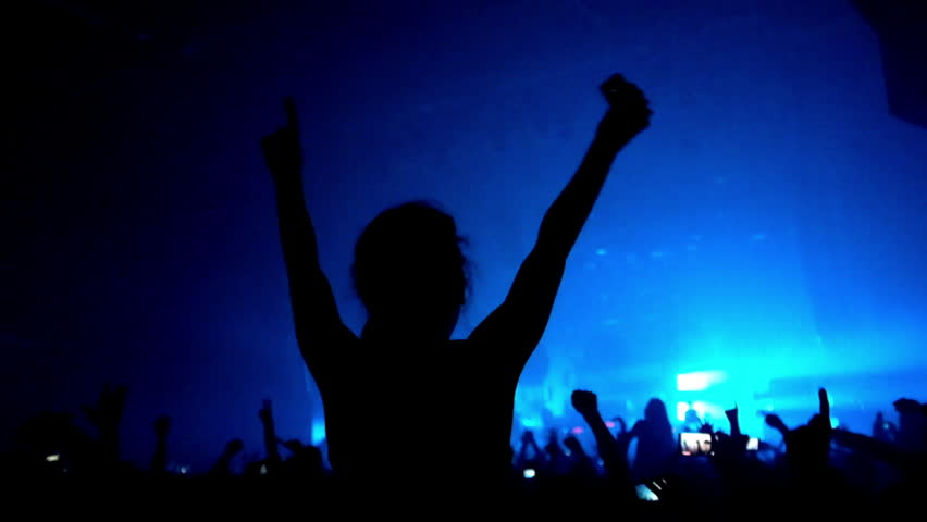 Fans waving their hands and hold the phone with digital displays the crowd at a rock concert.Here is  footage of people crowd partying at a concert or a night club.