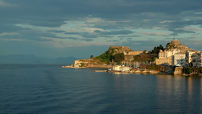 sailing along the Corfu at sunset, boat sailing along the islands at sunset, the island of Corfu in the rays of the evening sun, Storm over sunlit island of Corfu, Harbor view in Corfu in Greece