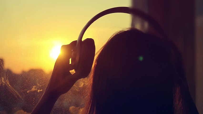Attractive Young Woman Wears Headphones Listening To Music On The Player At Blurred City Background Enjoying Tunes In Slowmotion Sunset