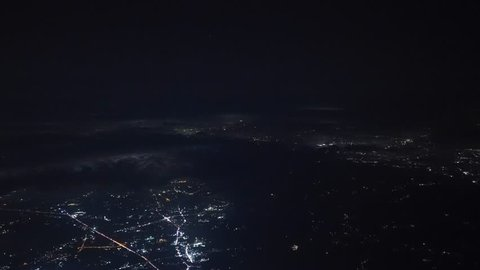 The 4K time-lapse footage of Aircraft cockpit view making an approach, descending through the night light city scene, to land at night at the shoreline airport.