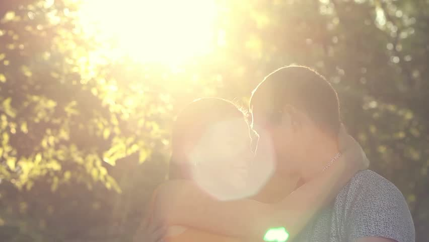 Romantic young couple in love sit together in park at sunset light background. Woman and man hugging, smiling, laughing, kissing. Sunset happy people portrait. Real time full hd video footage. | Shutterstock HD Video #12211667