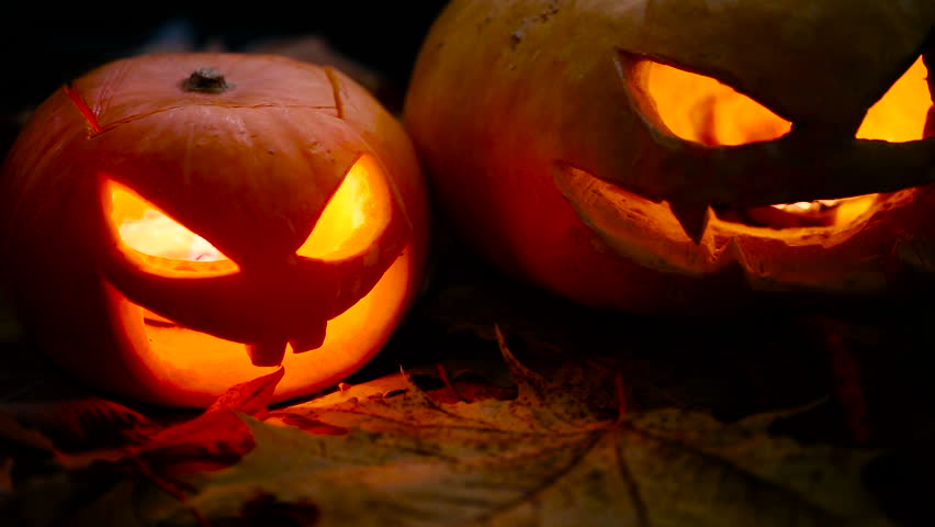 Two pumpkin lantern light in the darkness closeup. | Shutterstock HD Video #12214034