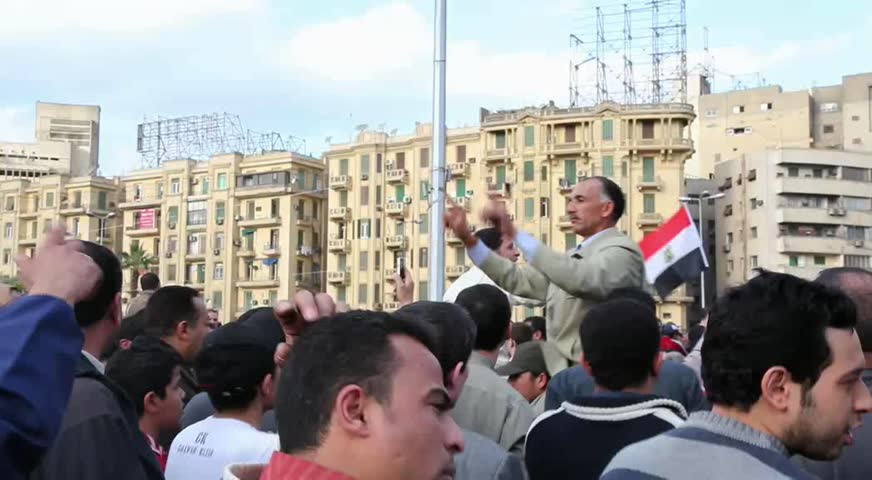 CAIRO - CIRCA JAN 2011: Man guides protesters in Tahrir Square, circa January 2011, Cairo, Egypt. Tahrir Square was the focal point of the 2011 Egyptian Revolution where demonstrations grew to 250,000 plus people by day 6, January 31, 2011.