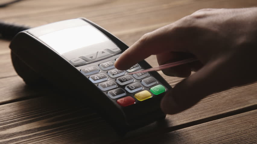 Man's hand pushing the button and swipe credit card payment on pos terminal standing on wooden desk.