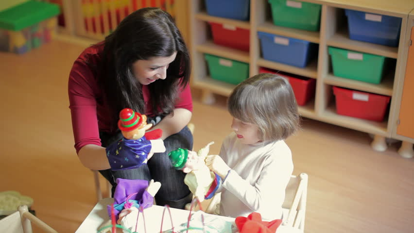 School: girl and teacher playing with marionette in kindergarten. Sequence