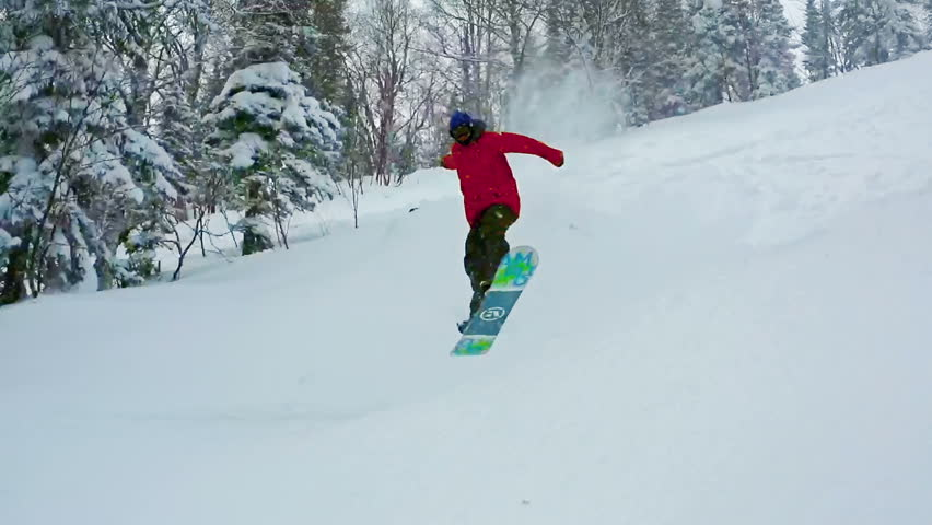 Snowboard freerider performing a jump on un-groomed terrain