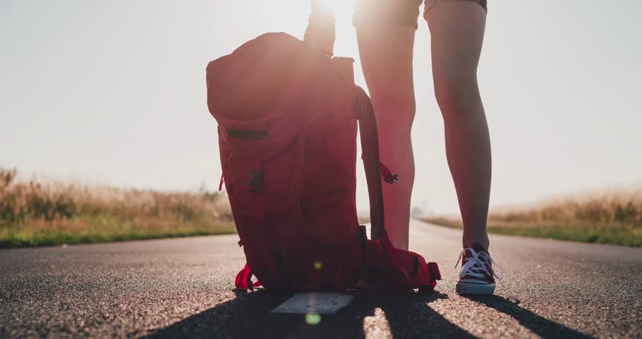 Traveler woman picking up her backpack. Backpacker woman lifts her bag from the road in the morning countryside background. Slow motion, 120 fps. 4K, DCi. Europe, Poland, Lower Silesia. | Shutterstock HD Video #12254087