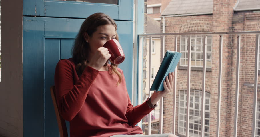 Beautiful woman at home drinking coffee using digital tablet happy wearing pajamas looking out of window loft apartment