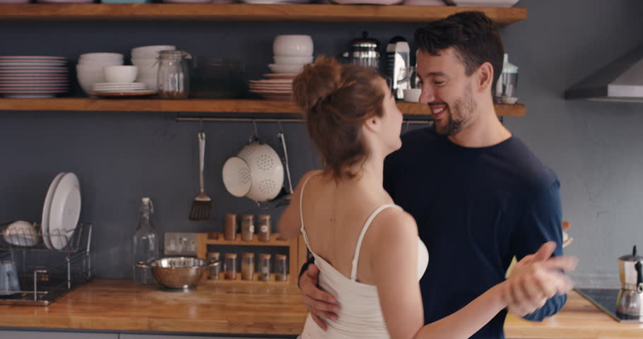 Morning at home happy young couple newly wed dancing listening to music in kitchen wearing pajamas in love having fun | Shutterstock HD Video #12270200