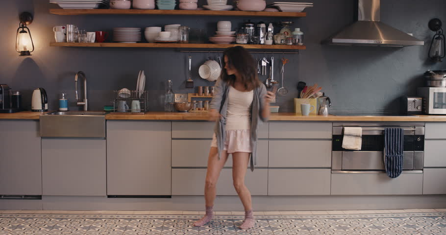 Happy young woman dancing in kitchen wearing pajamas in the morning listening to music on smartphone and coffee at home