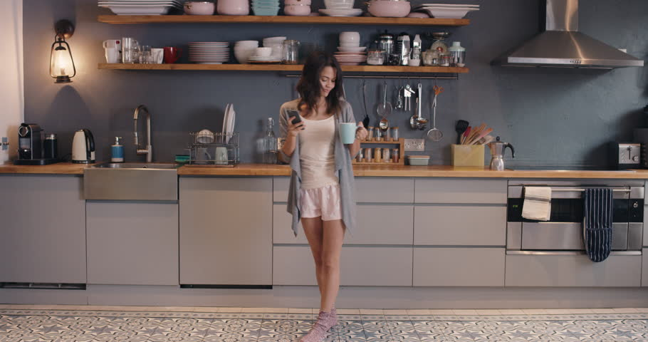 Happy young woman dancing in kitchen wearing...