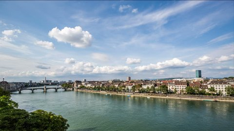 BASEL, SWITZERLAND – August 18, 2015: Basel skyline with, river, waterfront, sky and clouds timelapse City skyline by day
