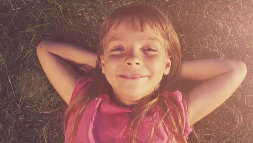 Point of view: Little girl is lying on the grass laughing and grimacing on a sunny day in the garden. Slow Motion 240fps. Happy childhood concept.