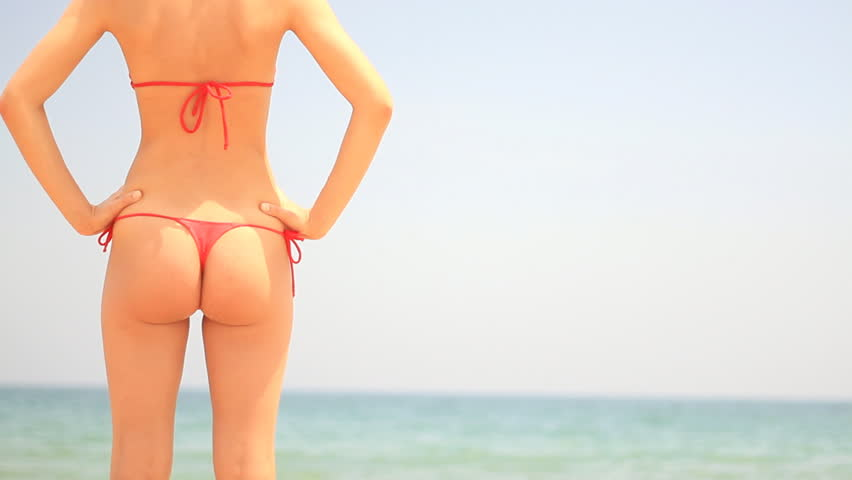 Sexy female buttocks in thong bikini on a background of the tropical sea