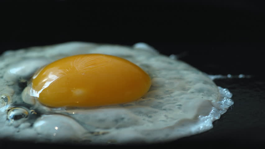 Cooking egg on fry pan. Shot with high speed camera, phantom flex 4K. Slow Motion.