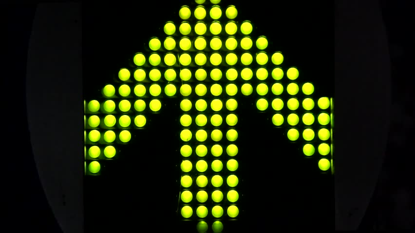 Green LED light arrow pointing up and moving fast upwards large arrow exists of 120 smaller LED lamps all moving by blinking turning on turning off black dark background fast moving lights up signal