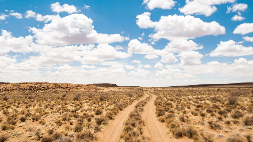 A scenic daytime drive time lapse on a gravel road with two dirt tracks in a grassy landscape setting with a blue sky and scattered clouds, front point of view. 4K
