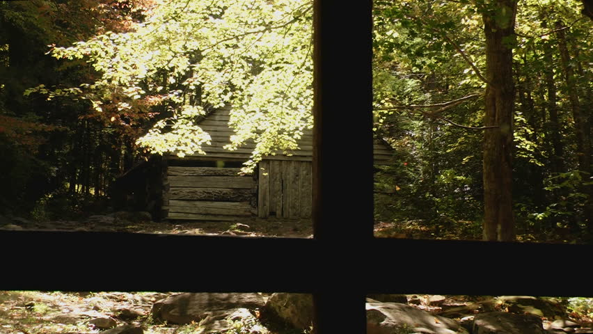 Rustic cabin in early autumn in the Great Smoky Mountains with dark shadows and some autumn color as seen from a window pane from another historical cabin
