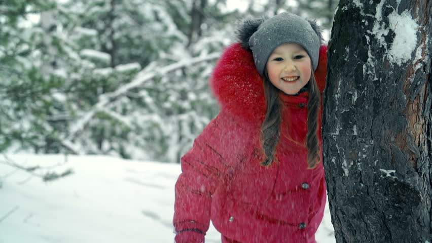 Cheerful little girl hiding behind a tree trunk during snowball fight