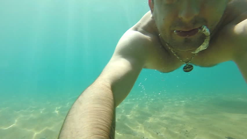 Man swimming underwater filming themselves on camera. | Shutterstock HD Video #12400607
