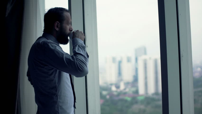 Young businessman drinking coffee and admire view from window  | Shutterstock HD Video #12412991