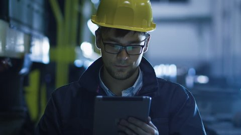 Technician in Glasses and Hard Hat Using Tablet in Industrial Environment. Shot on RED Cinema Camera in 4K (UHD).