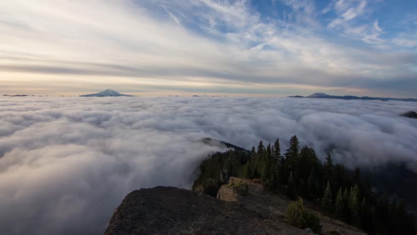 Time lapse footage from above the clouds with mount Adams and St. Helens in the background.