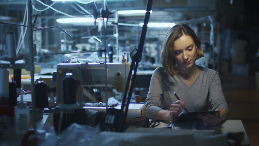 Young woman garment worker is using tablet with a stylus at a clothing factory during a night shift. Shot on RED Cinema Camera in 4K (UHD)   Shutterstock HD Video #12505787