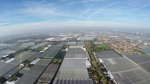 Aerial footage above a greenhouse glasshouse farm area industry for growing plants flowers and fruit requiring regulated climatic conditions blue sky and sun also showing small village glasteelt 4k