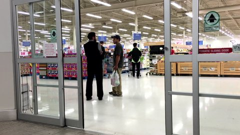 Coquitlam, BC, Canada - November 02, 2015 : People with Shopping Cart Walking Through the Doors at superstore in Coquitlam BC Canada with 4k resolution
