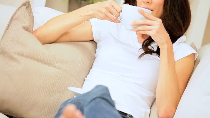 Caucasian female lying on her sofa drinking coffee