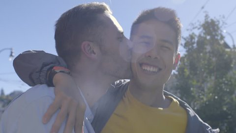 Closeup Of Happy Gay Couple Walking Down The Street In San Francisco, Man Kisses His Boyfriend On Cheek