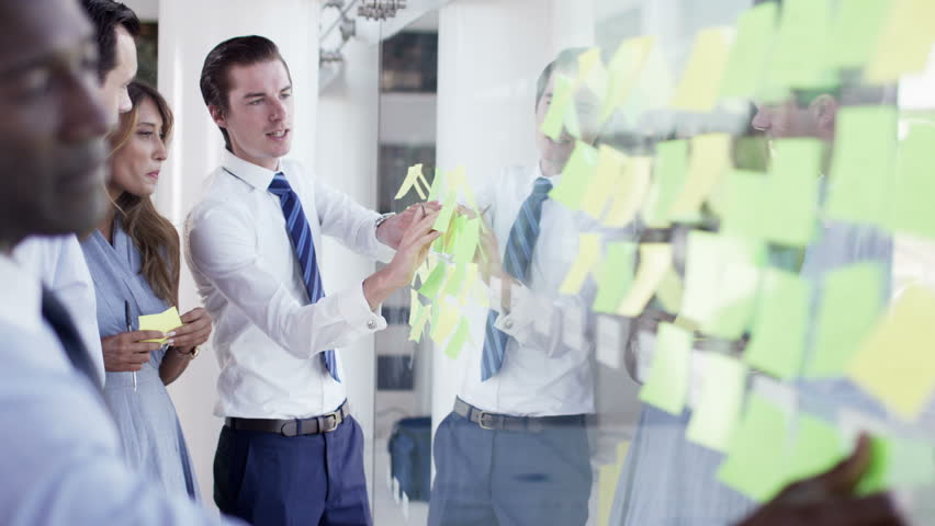 4K Attractive mixed ethnicity business team brainstorming for ideas with sticky notes in modern office. Shot on RED Epic.