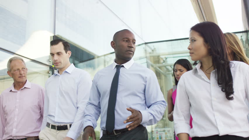 4K Attractive mixed ethnicity business team in conversation as they walk outside modern glass office building. Shot on RED Epic. | Shutterstock HD Video #12630395