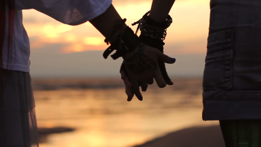 lesbians holding hands at sunset on the beach HD