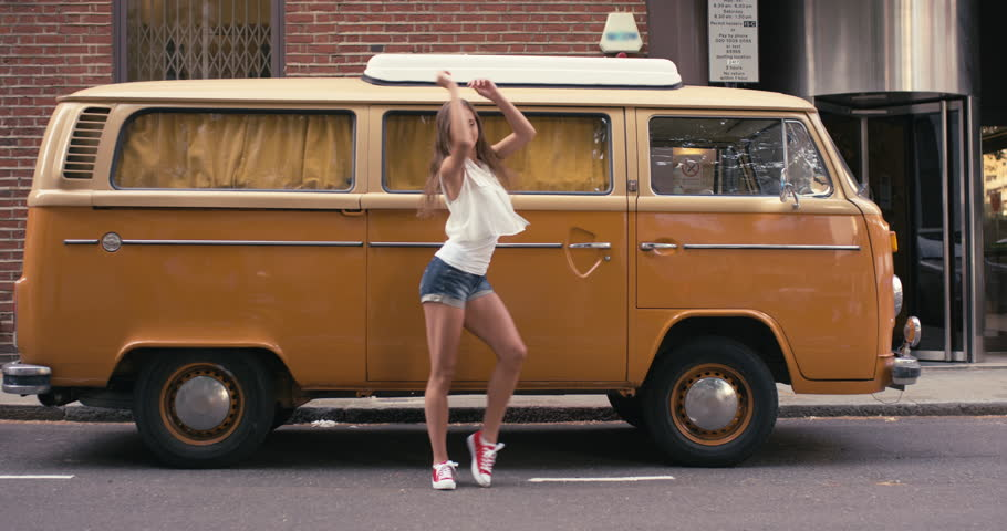 Contemporary happy funky caucasian woman street dancer vintage camper van dancing freestyle in the city hippie van