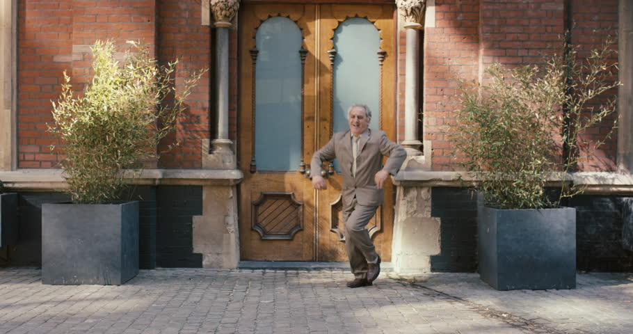 Happy elderly dancer man wearing suit in front of apartment funky street dancing freestyle in the city #12658727