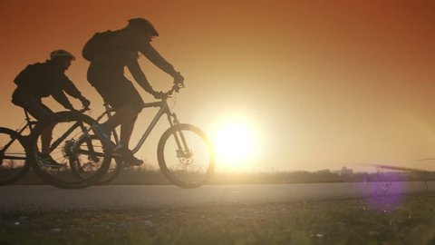 Two people riding bicycles on the background of an orange sunsetting sky