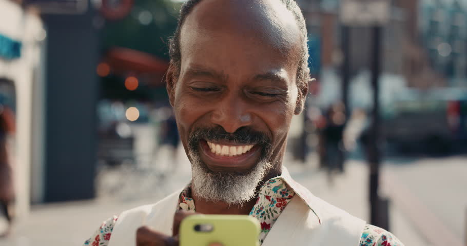 Slow Motion Portrait of mature african american man using smart phone sharing social media connection in city real people series