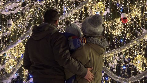 Family admiring decorations and lights of Christmas tree in city center