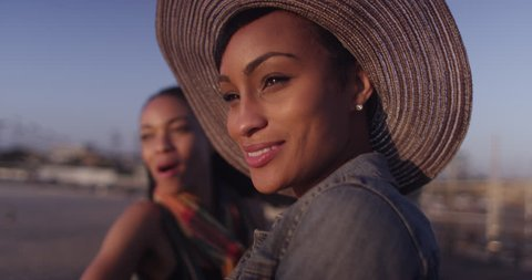 Black women best friends laughing and smiling while talking at beach