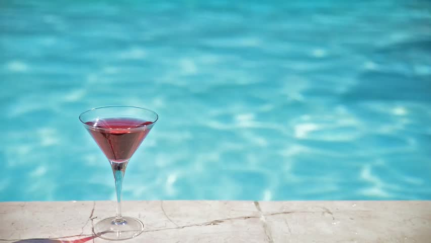 Young pretty woman swimming in a pool - Woman on vacation , cocktail standing next to a swimming pool in a tropical resort | Shutterstock HD Video #12695273