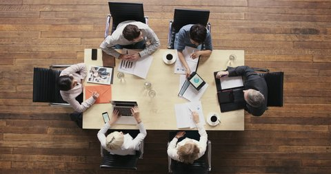Top view diverse business people meeting at boardroom table discussing financial report using graphs and big data in trendy shared office space