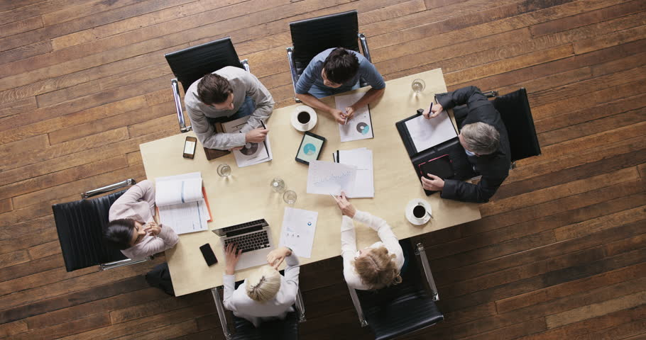 Top view diverse business people meeting at boardroom table discussing financial report using graphs and big data in trendy shared office space | Shutterstock Video #12707153