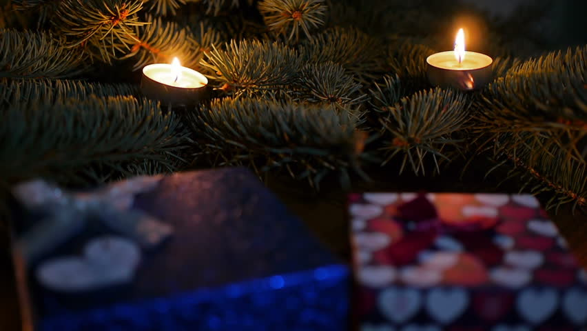 Christmas gifts under the tree with candles the lights on for 7 candle christmas decoration