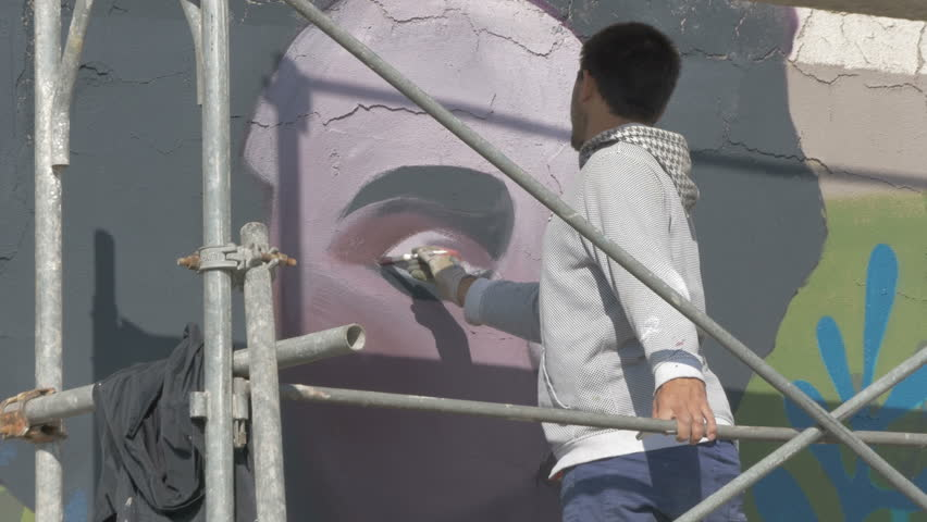 Artist On Scaffold Painting Graffiti Or Mural On The Wall With Brush, Close  Up. Part 55