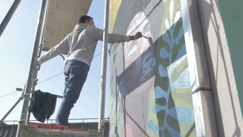 Young Artist Standing On Scaffold And Painting Mural Or Graffiti On  Building With Brush, Low Part 61