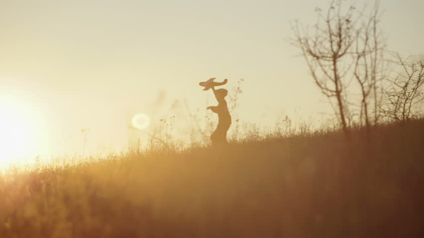 Boy with the airplane in the hands of running on a hill at sunset #12743387