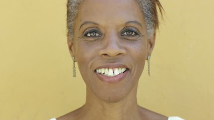 portrait of black 50 year old surprised woman with white hair, smiling on yellow background