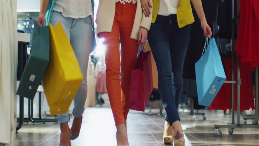 Low shot of female legs walking through a department store in colorful garments. Shot on RED Cinema Camera in 4K (UHD).